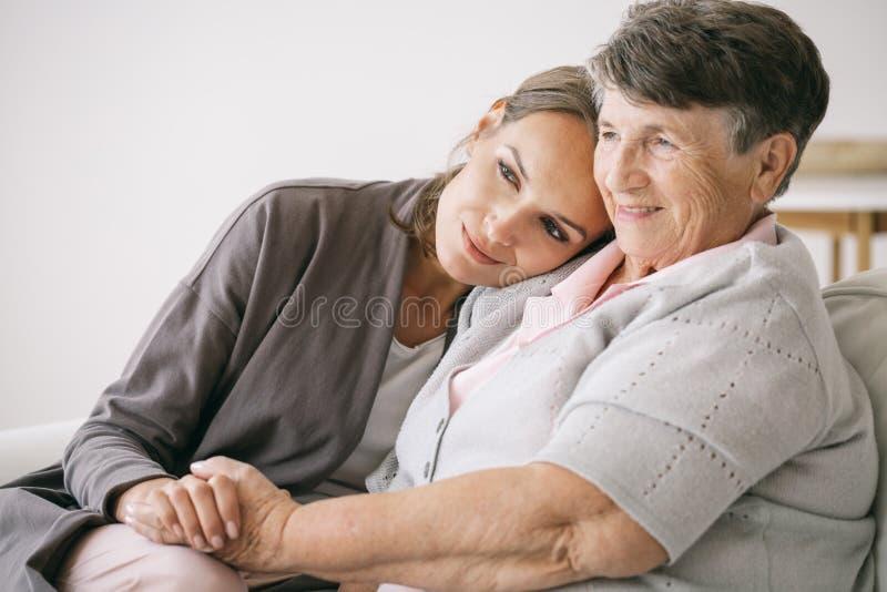 Woman hugging grandmother stock images