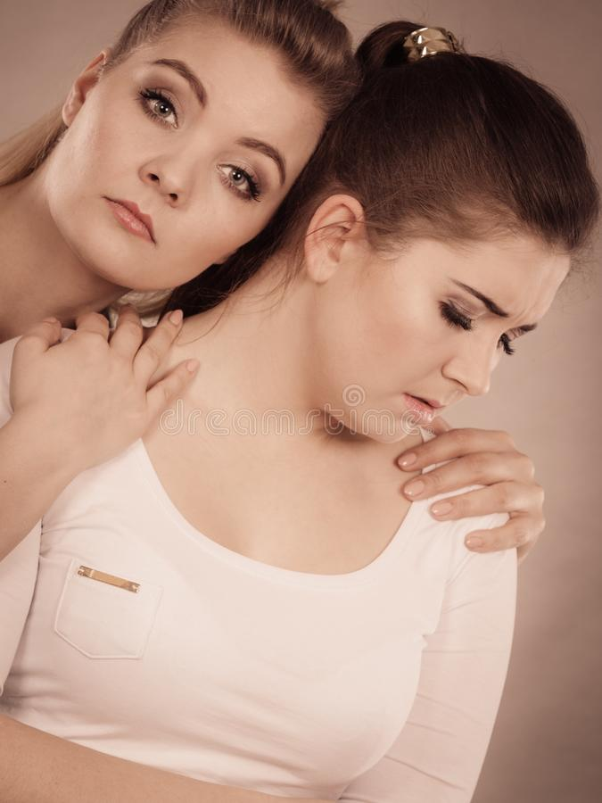 Woman hugging her sad female friend. Two female friend comforting each other during bad days being sad, hugging. Friendship concept royalty free stock photography