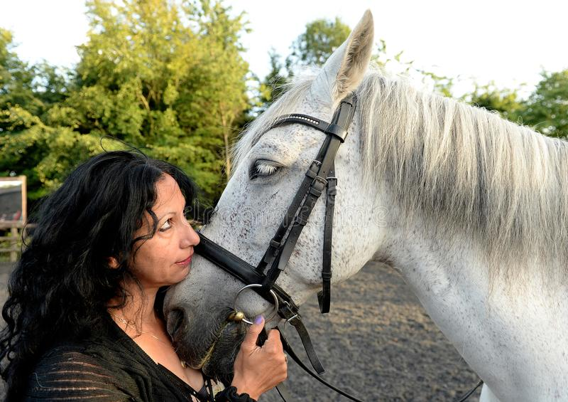 Woman hugging horse stock photo