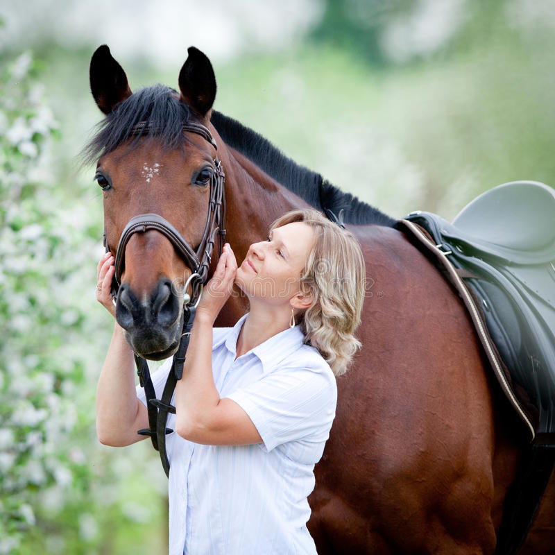 Woman hugging a horse. In springtime stock photo