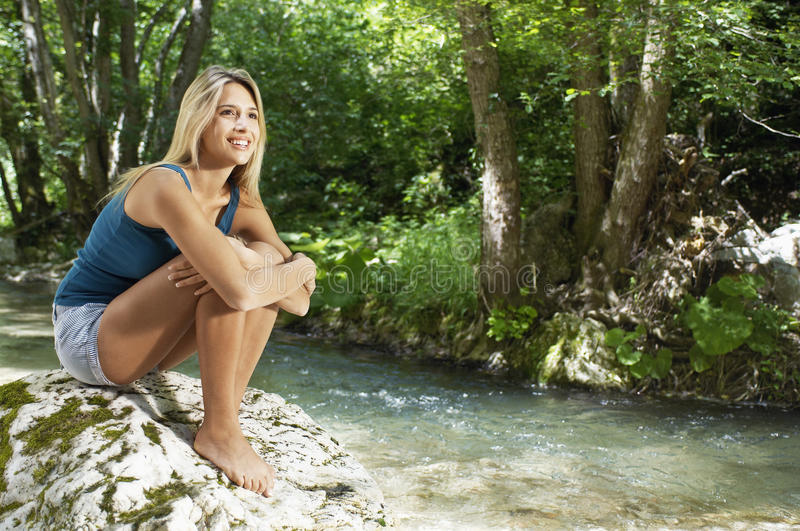 Download Woman Hugging Knees While Looking Away By Forest River Stock Image - Image: 31833419