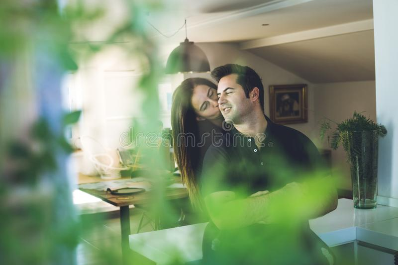 Woman hugging a man at home. Romantic concept of love and affection between couples stock photo