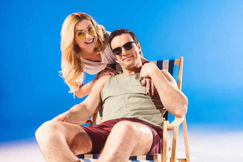 Woman hugging man relaxing in deck chair royalty free stock photography
