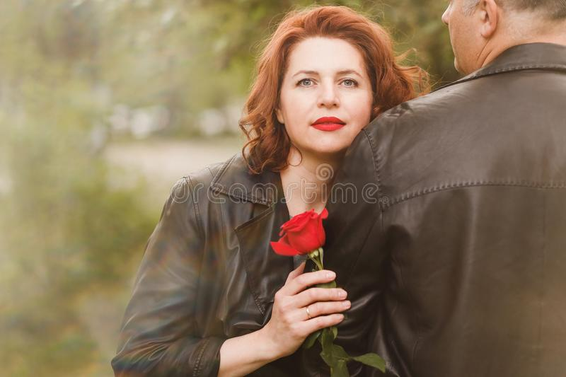 Woman hugging a man`s hand and holding a red rose stock photo