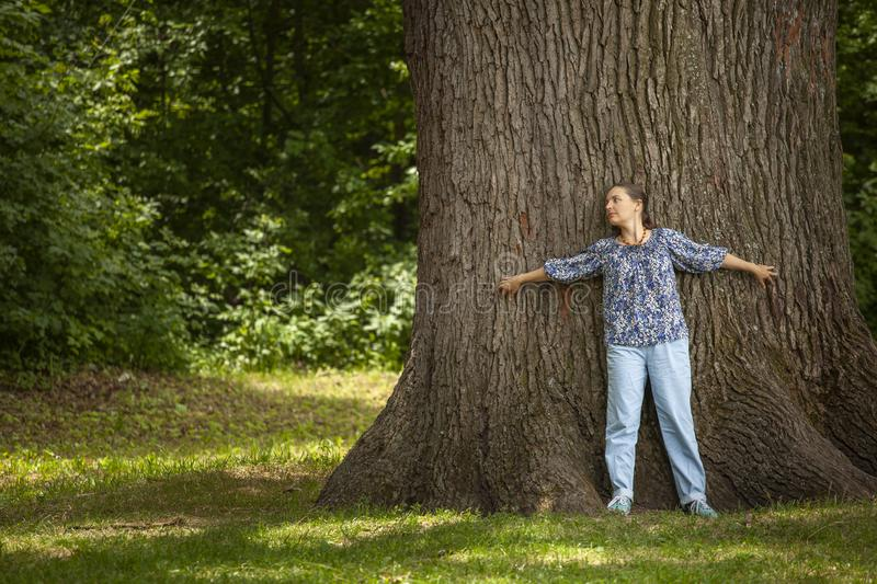 Woman hugging a old big tree in the summer forest, with love nature royalty free stock photography