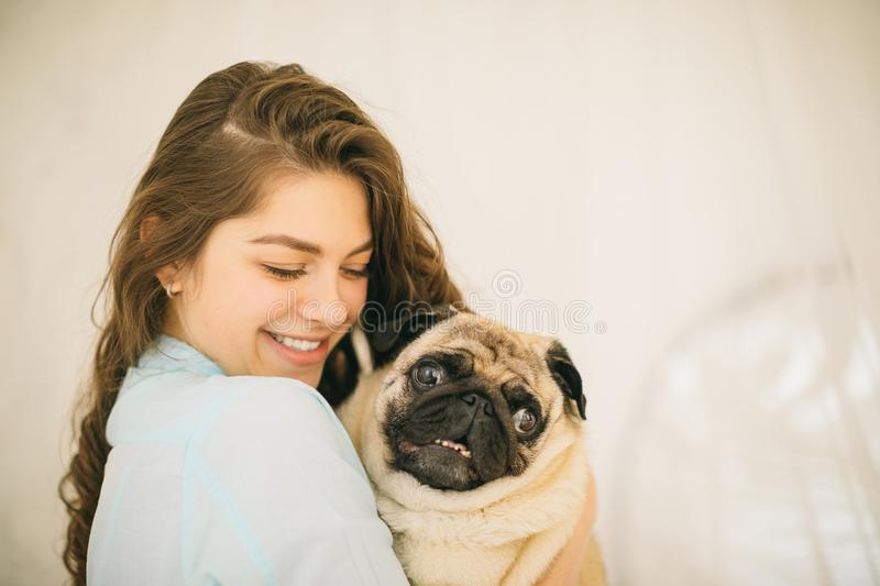 Woman hugging pet pug. Lovely family portrait royalty free stock images