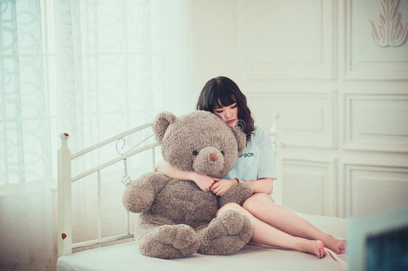 Woman hugging teddy bear on bed royalty free stock photos