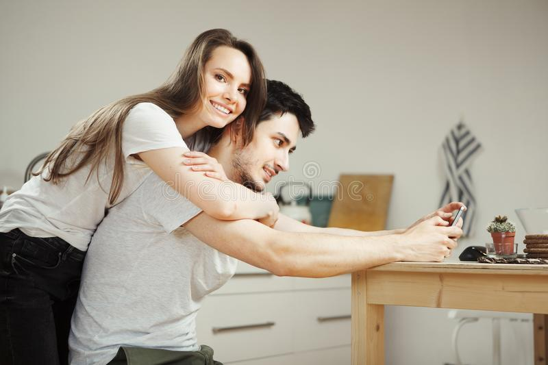 Woman hugs her man from back, tenderly embracing him stock image