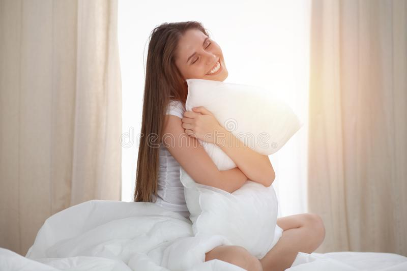 Woman hugs the pillow after wake up, entering a day happy and relaxed after good night sleep. Sweet dreams, good morning. New day, weekend, holidays concept royalty free stock images