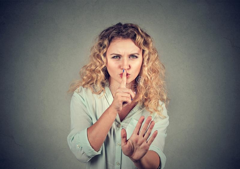 Woman with hush be quiet gesture on gray background. royalty free stock photo
