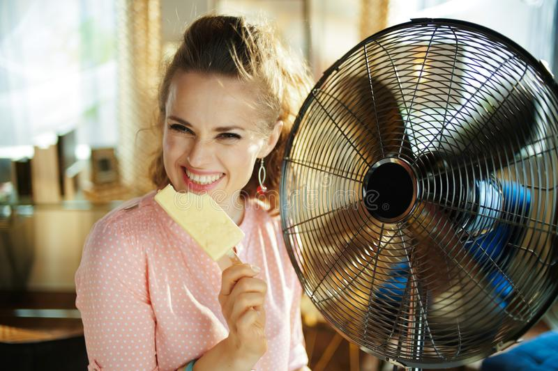 Woman with ice cream cooling down using electric metallic fan royalty free stock photos