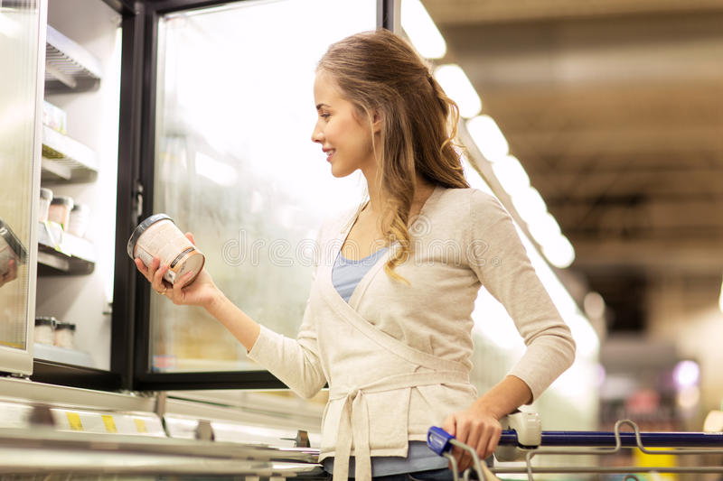Woman with ice cream at grocery store freezer. Sale, food, shopping, consumerism and people concept - woman with ice cream at grocery store freezer stock photo