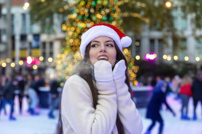 Woman on a ice rink on a Christmas market. Woman with a red Santa hat exhales the cold air on a ice rink on a Christmas market royalty free stock images