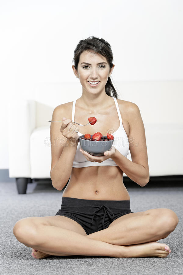 Woman ieating fruit in fitness clothes. Beautiful young woman in fitness clothes eating fresh fruit from a bowl at home royalty free stock image