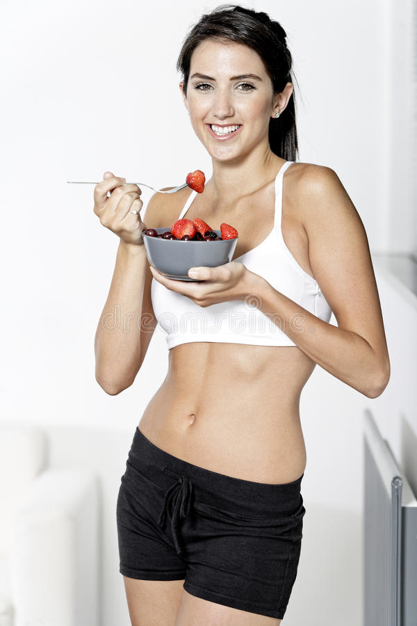 Woman ieating fruit in fitness clothes. Beautiful young woman in fitness clothes eating fresh fruit from a bowl at home royalty free stock images