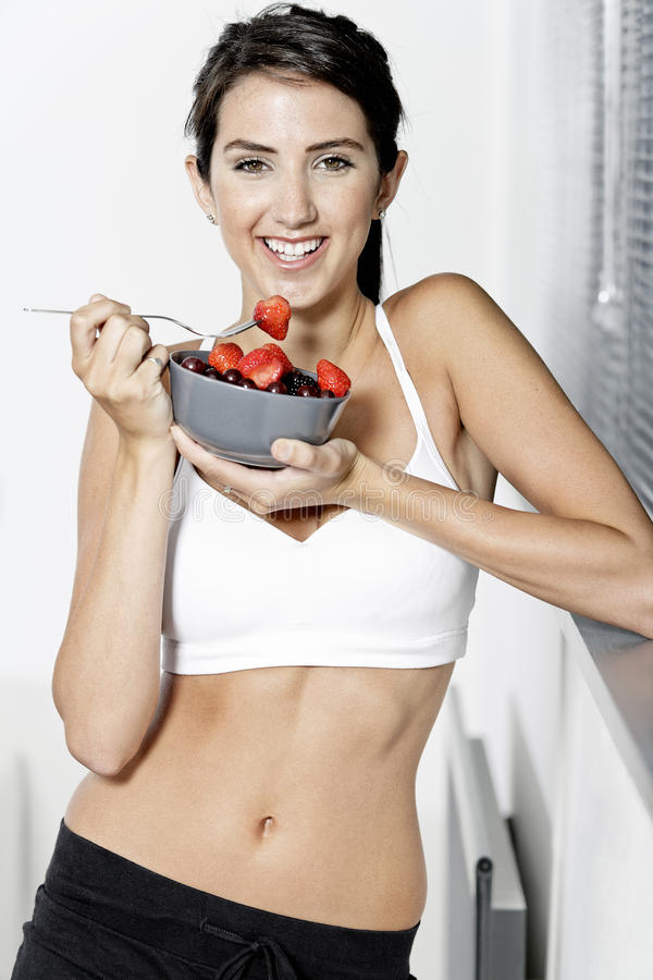 Woman ieating fruit in fitness clothes. Beautiful young woman in fitness clothes eating fresh fruit from a bowl at home stock photos