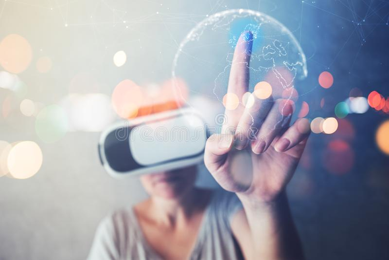 Woman immersed in virtual reality pointing to Sweden. And Scandinavia on world map, female person using modern VR headset to experience 3d multimedia content royalty free stock images