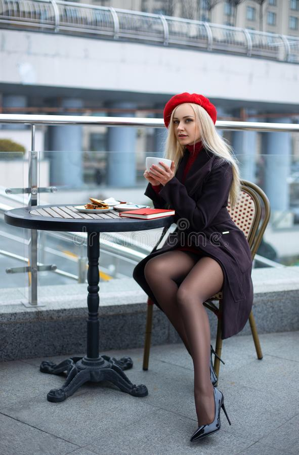 Free Woman In The Street Cafe In A Red Cap With Tea Cup Stock Photography - 164536072
