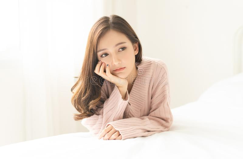 Woman indoor portrait. Closeup of pensive young Asain woman in warm knitted pink clothes in the bedroom. Negative human facial royalty free stock images