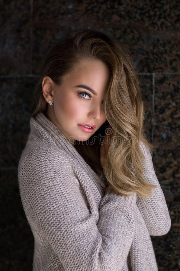 Woman indoor portrait. Young beautiful woman in warm knitted clothes at home. fashion. Autumn, winter stock image
