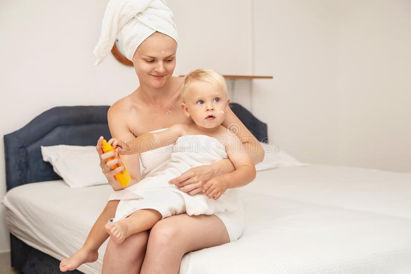 Woman and infant baby in white towels after bathing apply sunscreen or after sun lotion or cream. Children skin care in a hotel or. Bedroom. Spf, skin stock images