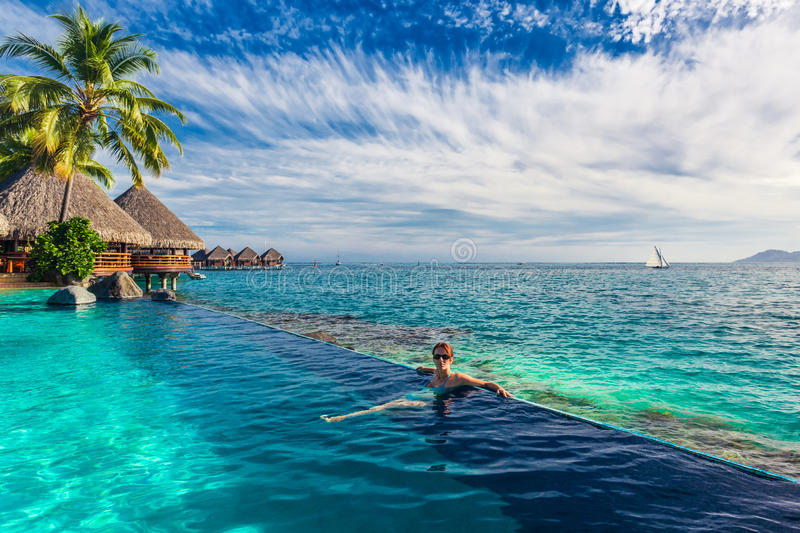 Woman in the infinity pool in exotic island resort with bunalows over water royalty free stock images