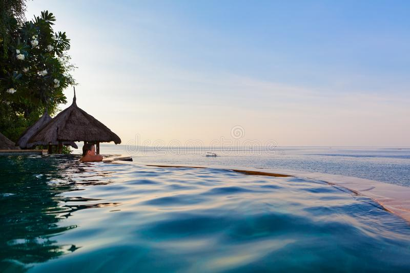 Woman at infinity swimming pool with sea view royalty free stock images