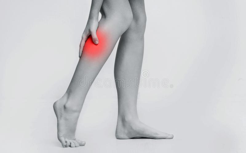 Woman with injured calf, massaging painful leg muscle. Black and white photo with red sore spot stock photos