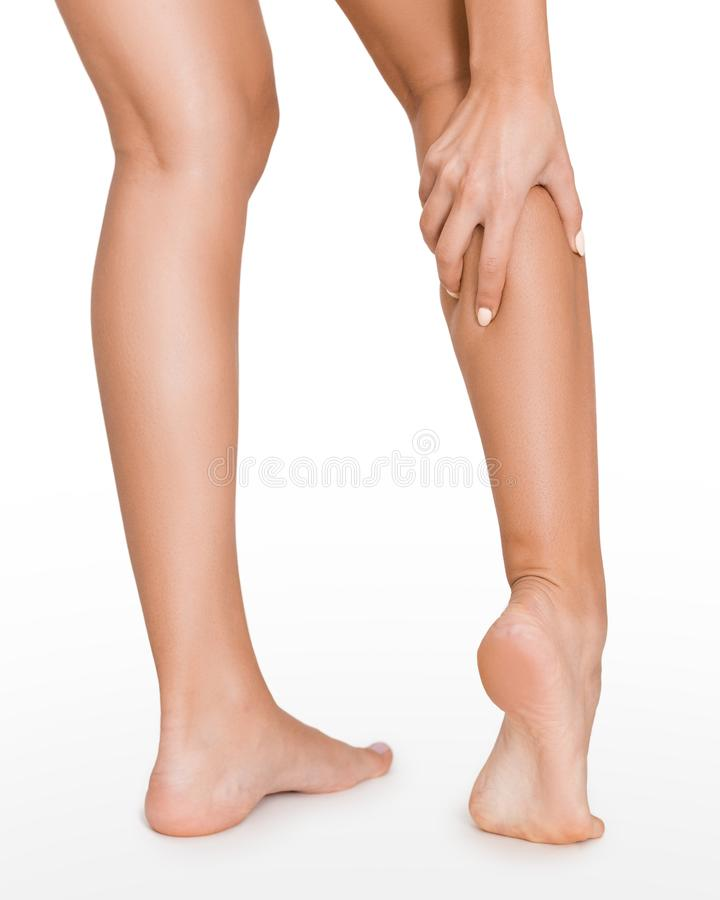 Woman with injured calf, massaging painful leg muscle. Isolated on white background stock photos