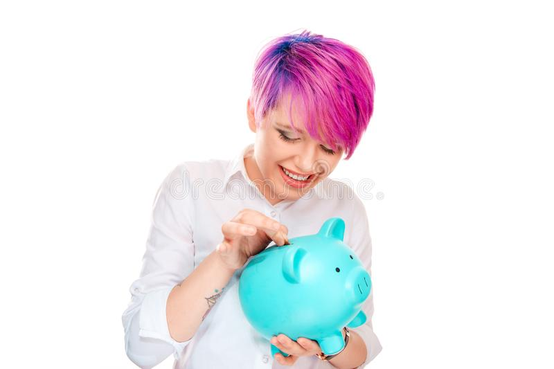 Woman inserting coin in a piggy bank. Isolated on white background. Millennial model with pink magenta hair. Saving concept stock photos