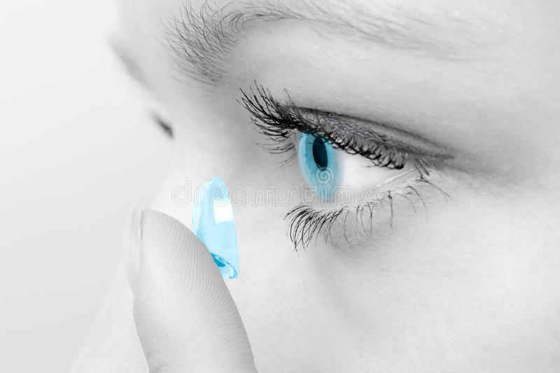 Woman inserting a contact lens in eye. royalty free stock photography