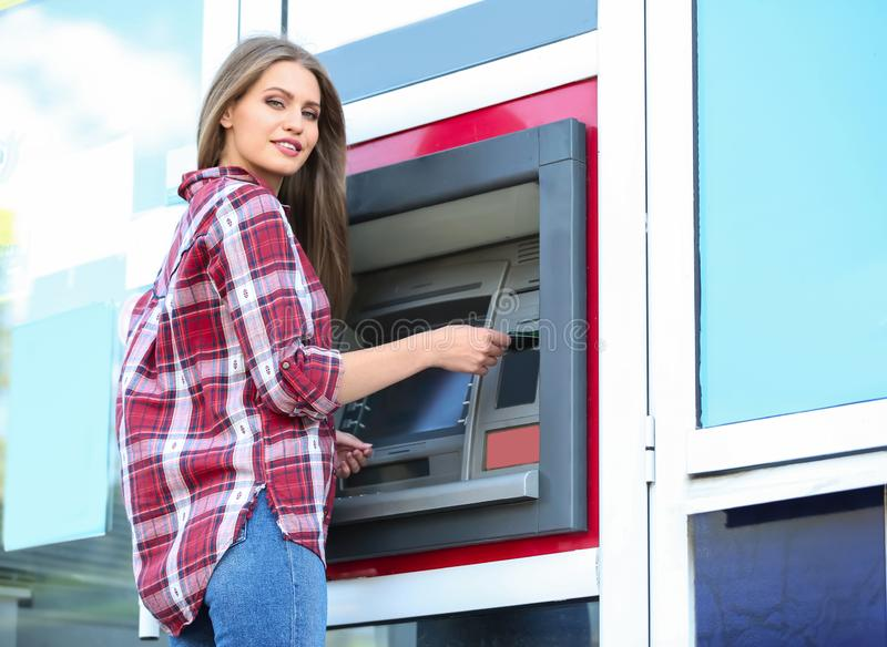 Woman inserting credit card into cash machine outdoors royalty free stock photography