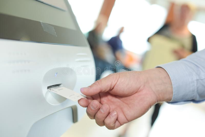 Woman inserting ticket into machine to pay for parking stock image