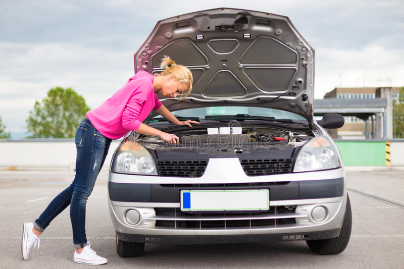 Woman inspecting broken car engine. Self-sufficient confident modern young woman inspecting broken car engine royalty free stock photography