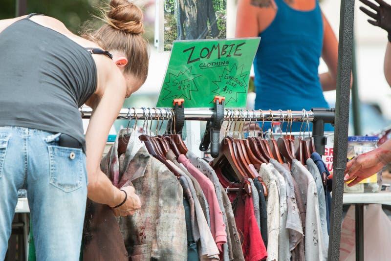 Woman Inspects Bloody Zombie Clothing Before Atlanta Pub Crawl. Atlanta, GA, USA - July 25, 2015: A woman looks over a rack of torn and bloody zombie clothing royalty free stock photos