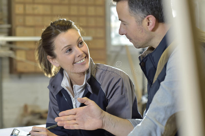 Woman and instructor in carpentry workshop stock photos