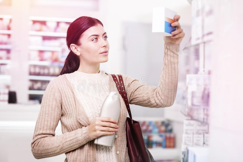 Woman interested in information on a box of medication. Information on a box. Woman with a red purse keeping a bottle in her hand and interested in information stock images