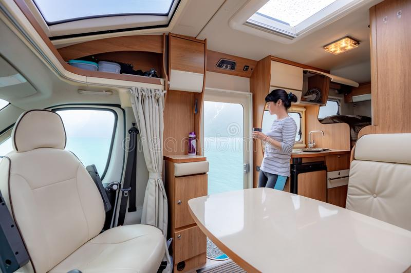 Woman in the interior of a camper RV motorhome with a cup of coffee looking at nature stock image