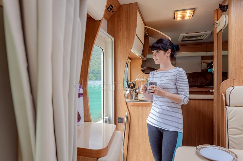 Woman in the interior of a camper RV motorhome with a cup of coffee looking at nature stock images