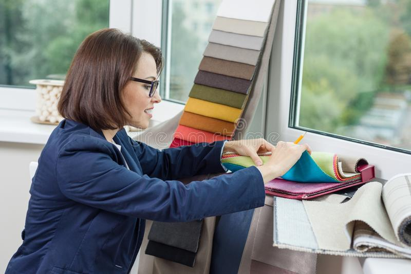 Woman interior designer, works with samples of fabrics for curtains and blinds. royalty free stock photos