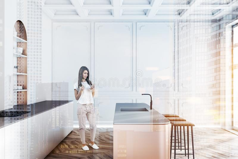 White kitchen with cupboard, woman. Woman in interior of modern kitchen with white walls, wooden floor, white countertops with cooker, beige island with sink and royalty free stock photography