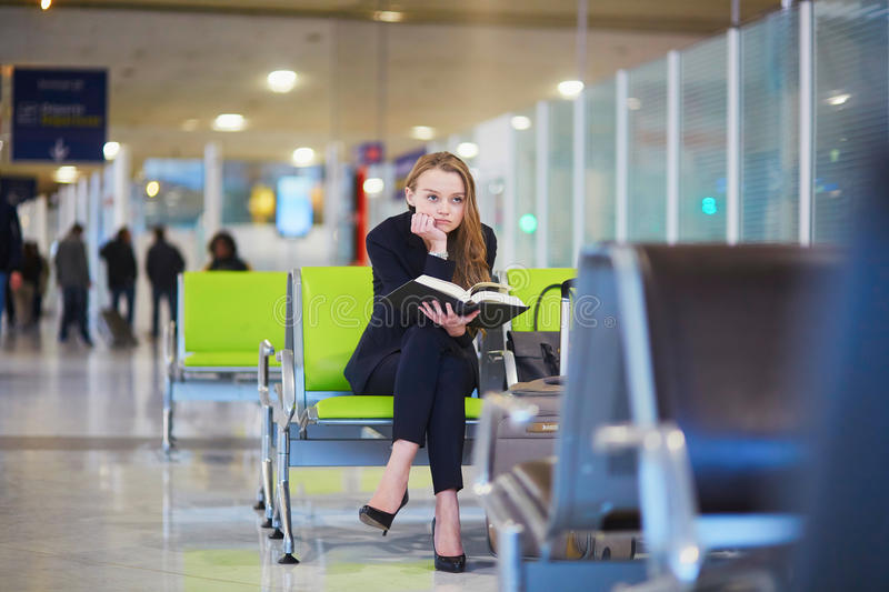 Download Woman In International Airport Terminal, Reading Book Stock Photo - Image: 83723639