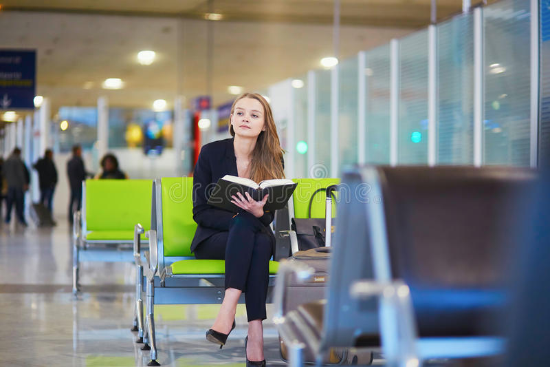 Woman in international airport terminal, reading book stock images