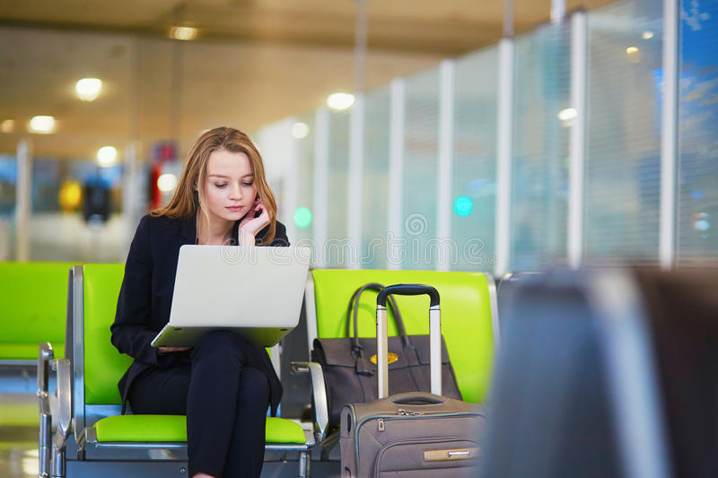 Woman in international airport terminal, working on her laptop. Young elegant business woman with hand luggage in international airport terminal, working on her royalty free stock images