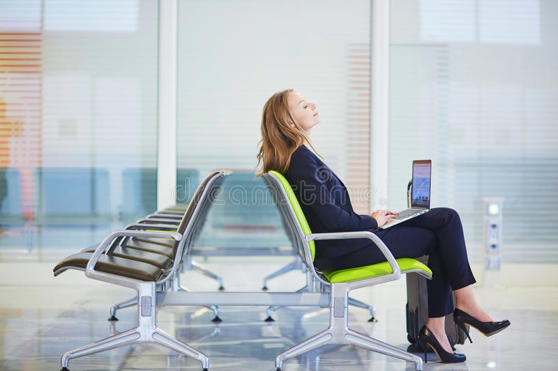 Download Woman In International Airport Terminal, Working On Her Laptop Stock Photo - Image: 83723587