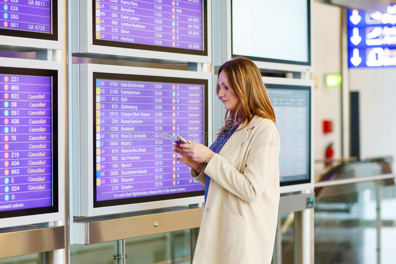 Woman at international airport waiting for flight. Tired woman at international airport with tickets and passport checking mobile for flight. Annoyed passenger stock photos