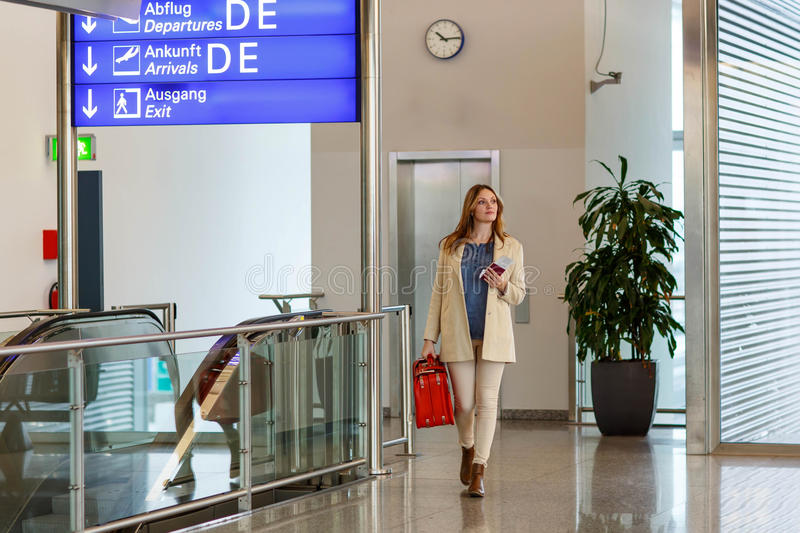 Woman at international airport waiting for flight. Tired woman at international airport walking through terminal. Angry passenger waiting. Canceled flight due to royalty free stock images