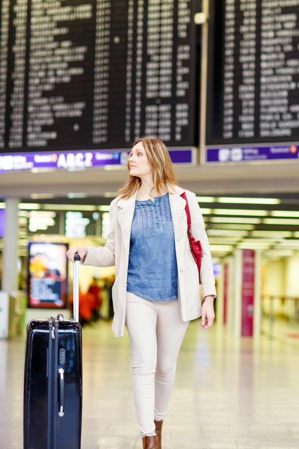 Woman at international airport waiting for flight. Tired woman at international airport walking through terminal. Angry passenger waiting. Canceled flight due to royalty free stock image