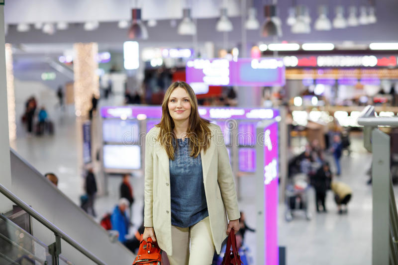 Woman at international airport waiting for flight. Tired woman at international airport walking through terminal. Happy passenger at stairs. Canceled flight due royalty free stock image