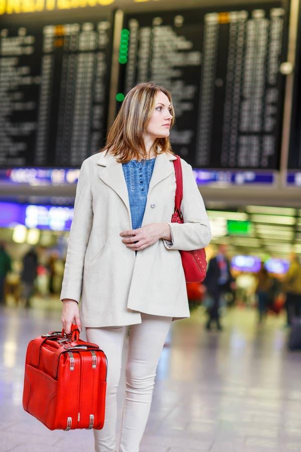 Woman at international airport waiting for flight. Tired woman at international airport walking through terminal. Upset tourist passenger waiting. Canceled stock image